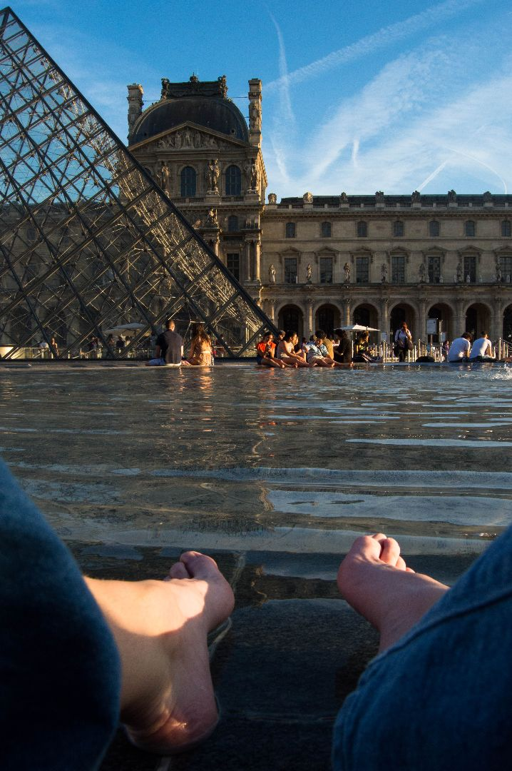 Rachel's feet with the Louvre in the background in Paris