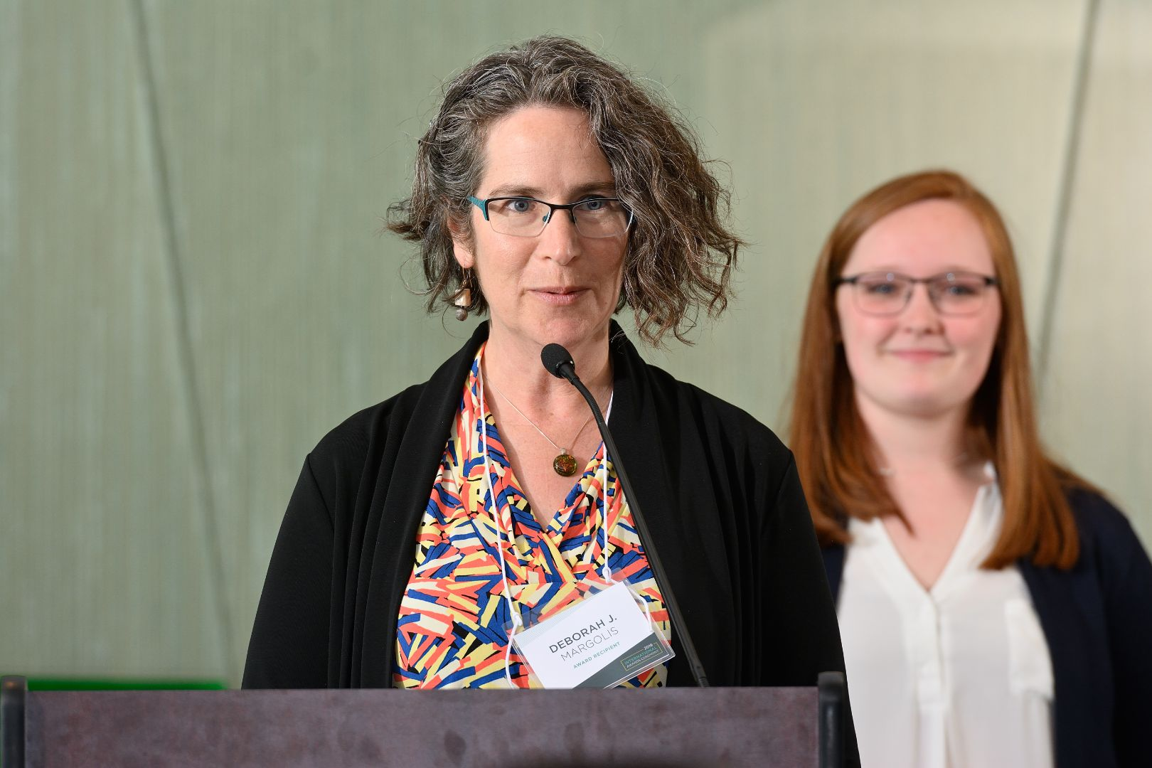 Deborah Margolis [female] standing at podium to receive award. MSU student Emily Skupin stands behind her.