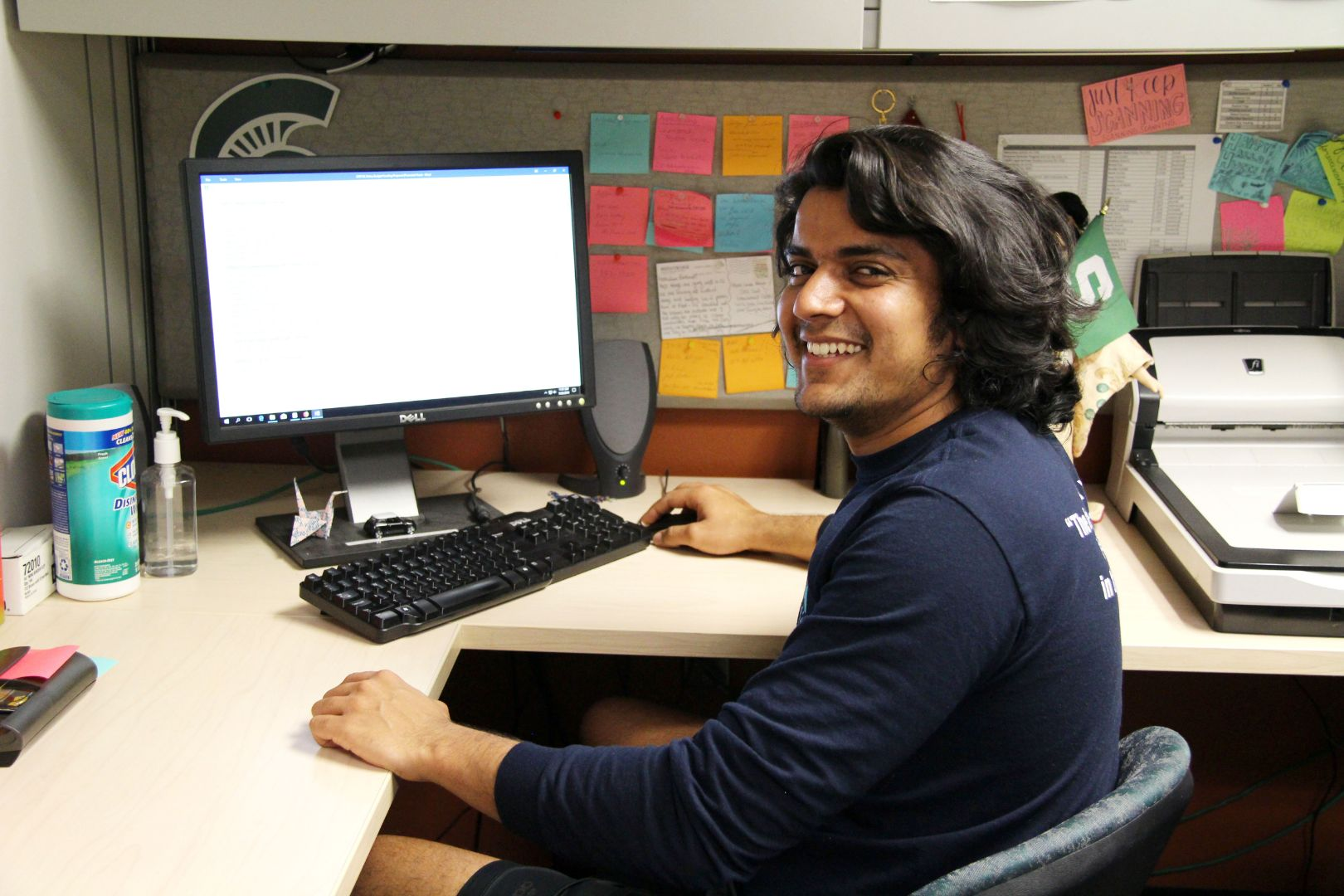 Abhimanyu Kinha sitting at desk in front of a computer. He is facing the camera and smiling. He works in the office of OISS in the MSU International Center.