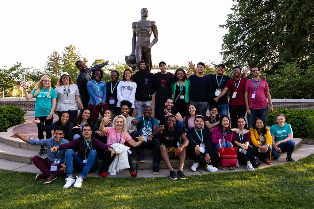 Group of delegates smiling as they pose for a photo at Sparty Statue on the campus of MSU