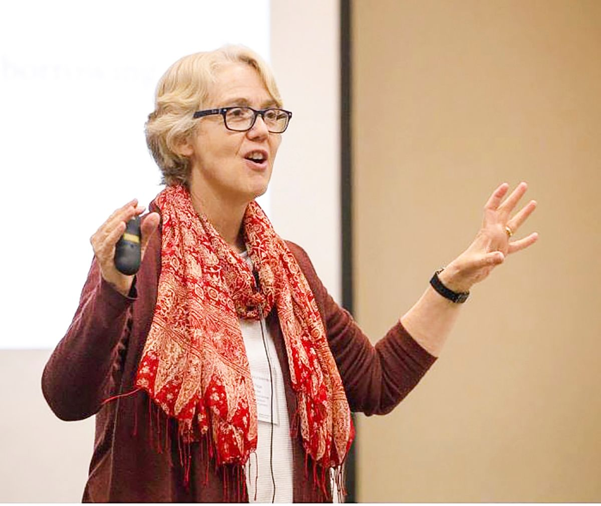 Lynne Paine in front of a projector screen, speaking and holding a PowerPoint clicker.