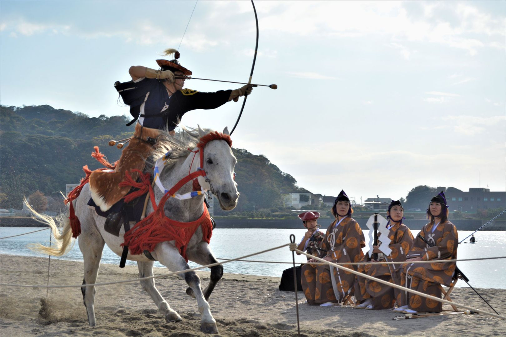 On a beach in Japan, a man sits atop a horse with his bow drawn, aimed at an unseen target. A group of people sit nearby, watching.