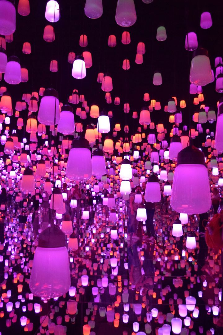 Dozens of lamps in various shades of purple, orange and pink hang and are reflected in a mirrored room.