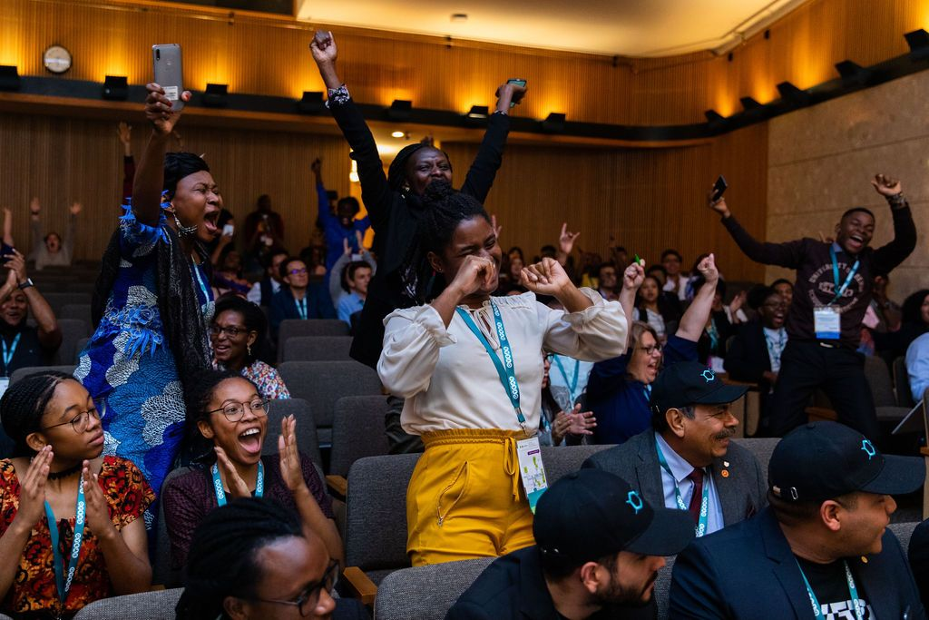 Group of people in the auditorium of the Kellogg Center cheering, clapping and smiling at GYAS competition.