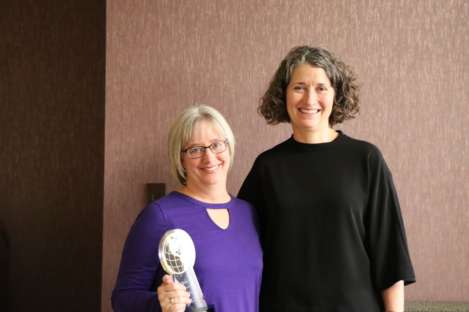 Two women standing together, one holding her Globie Award trophy.