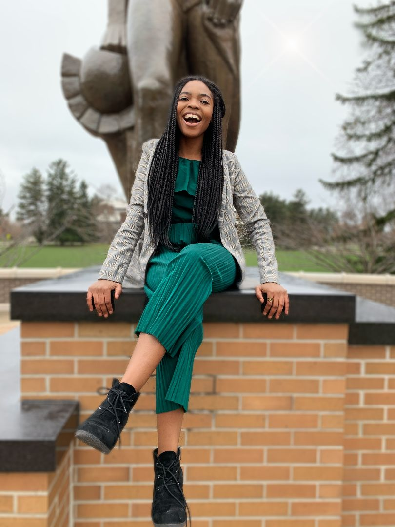 Abii-Tah Bih sits at the feet of the Sparty statue, smiling widely.