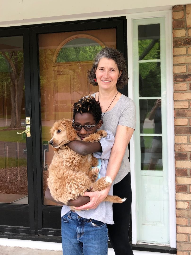 Krista McCallum Beatty is pictured with her son standing outside their front door. Her son is holding a dog.