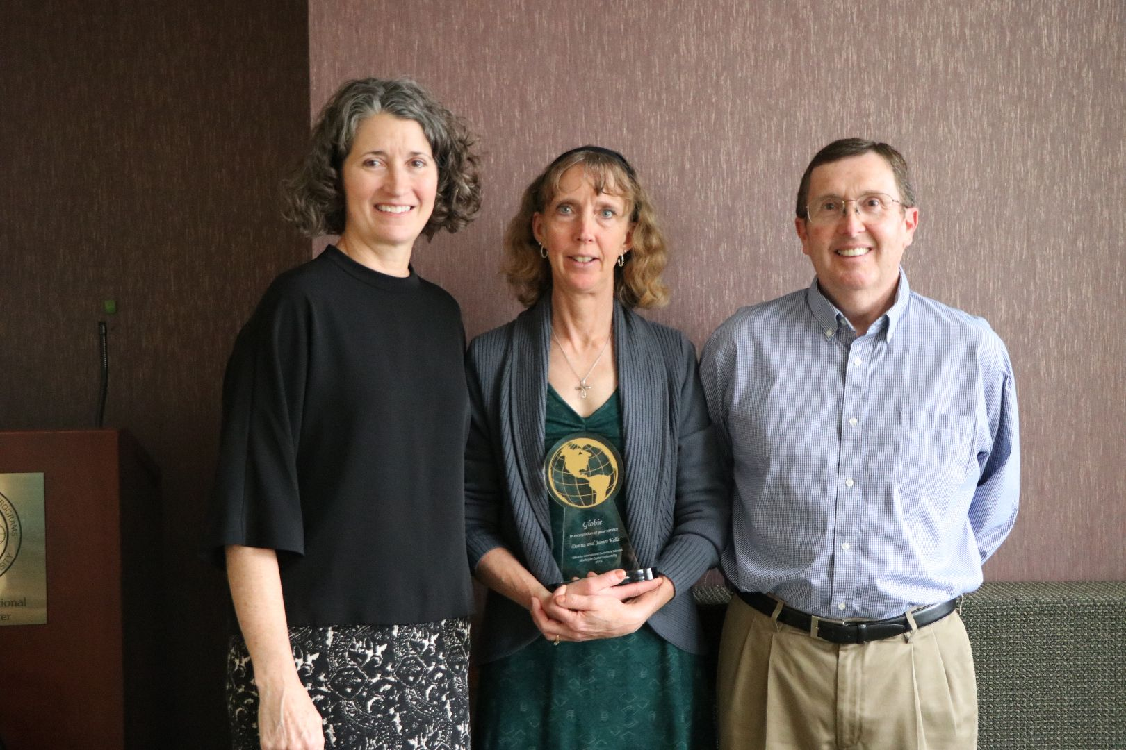 Two women and one man stand together, couple is receiving their Globie Award trophy.