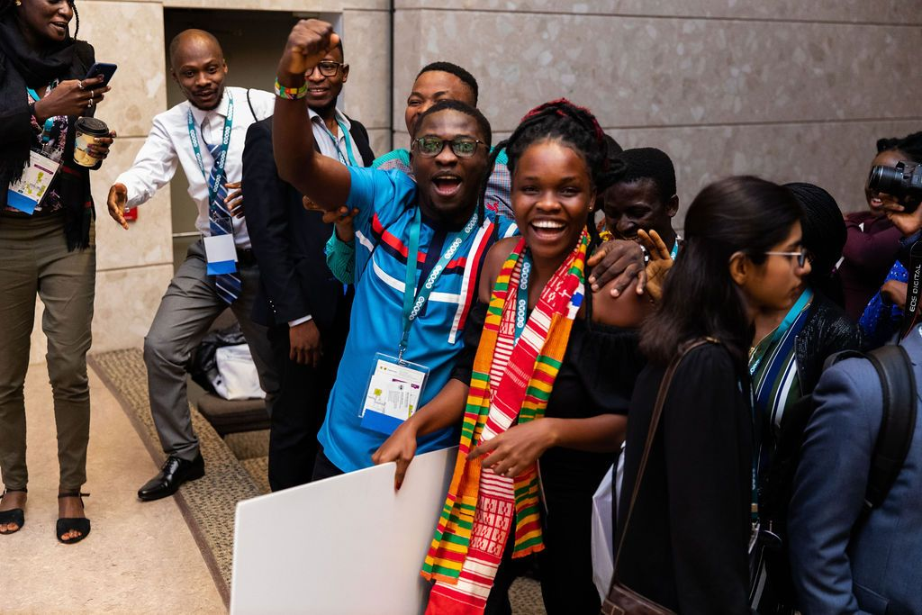 Male wearing blue shirt has a fist bump as he smiles while standing with Barbara Agyapong (female from Ghana) who is the founder of BidiGreen. She won first place. Both male and female are smiling.