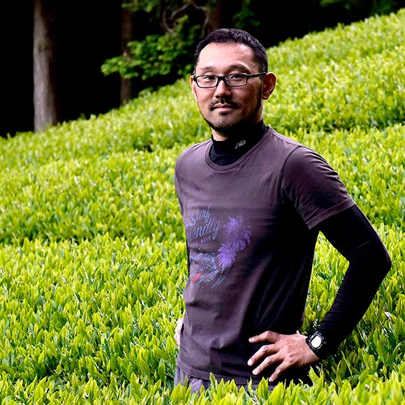 a man standing in front of green tea plants