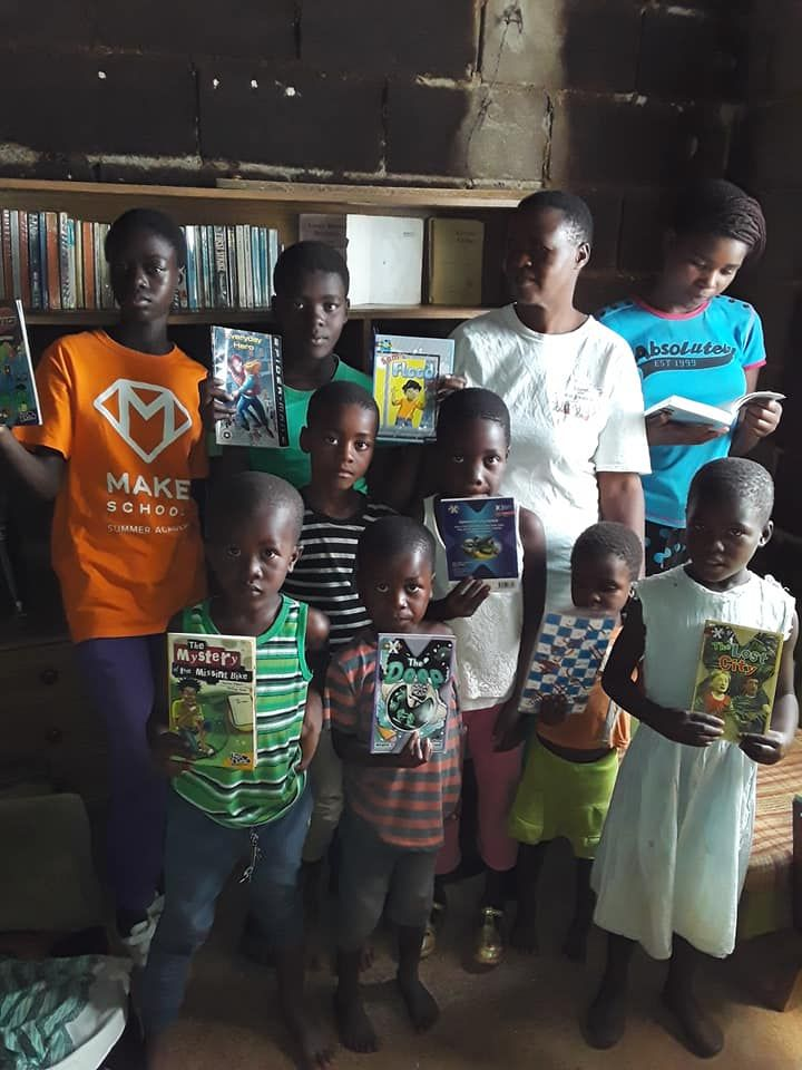 A group of eight youth in Zimbabwe stand together posing with books