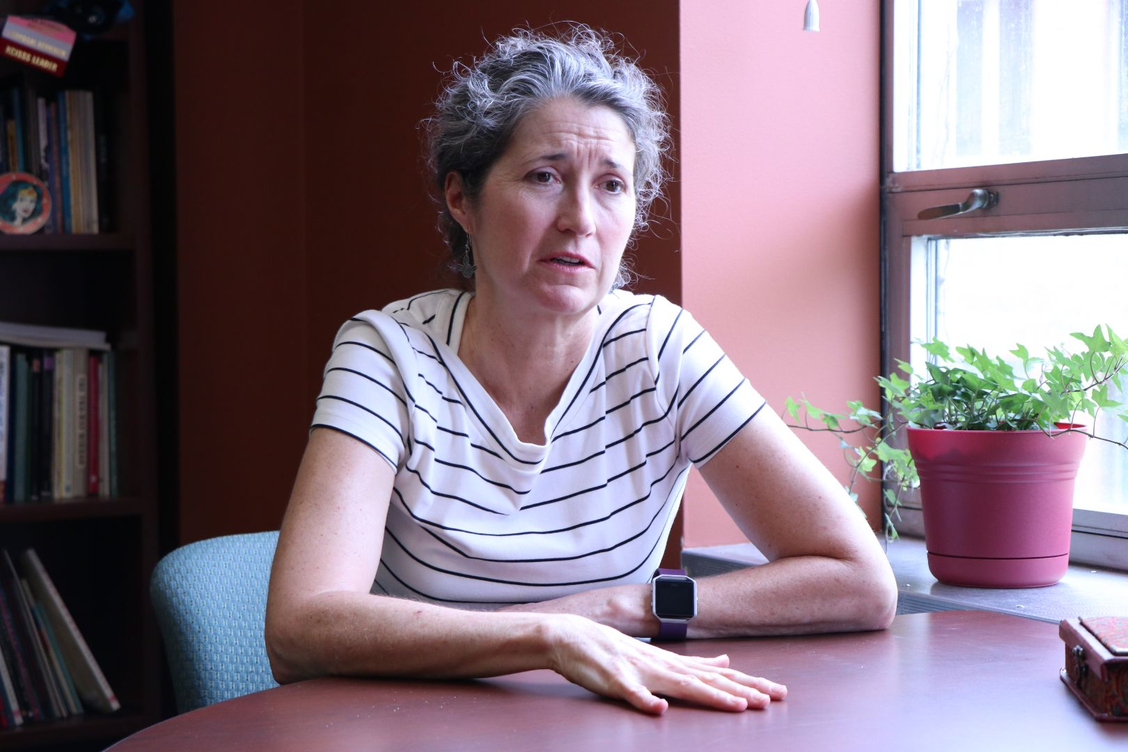 Photo of OISS director Krista McCallum Beatty sitting in her office speaking to a colleague