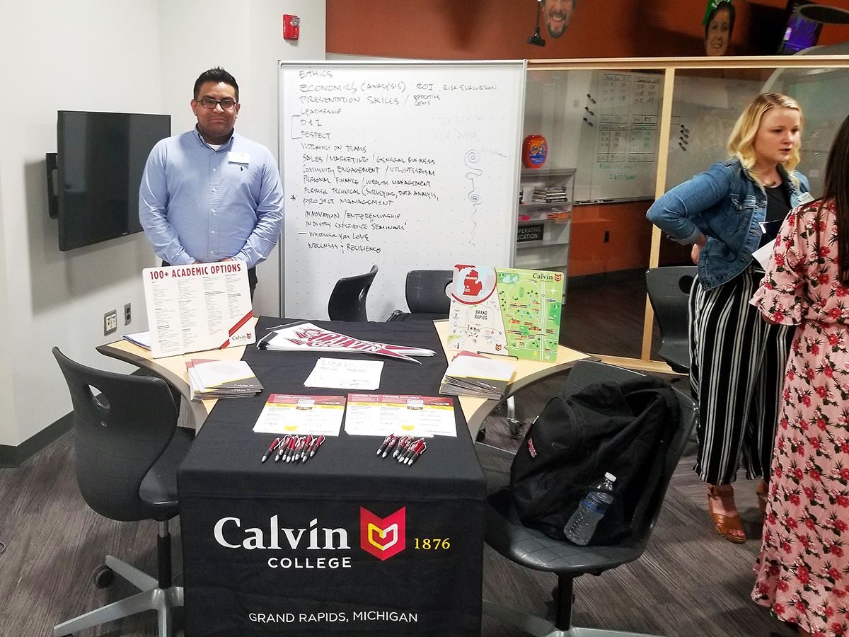 Representative from Calvin College at MSU {male standing in front of a table with Calvin College information on table}