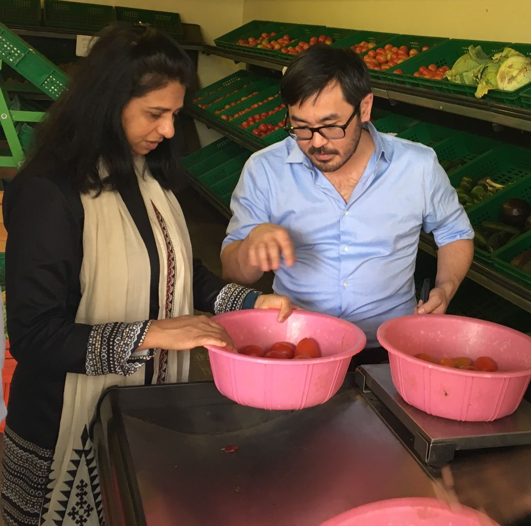 Mywish Maredia with a male colleague, inspecting a bowl of vegetables