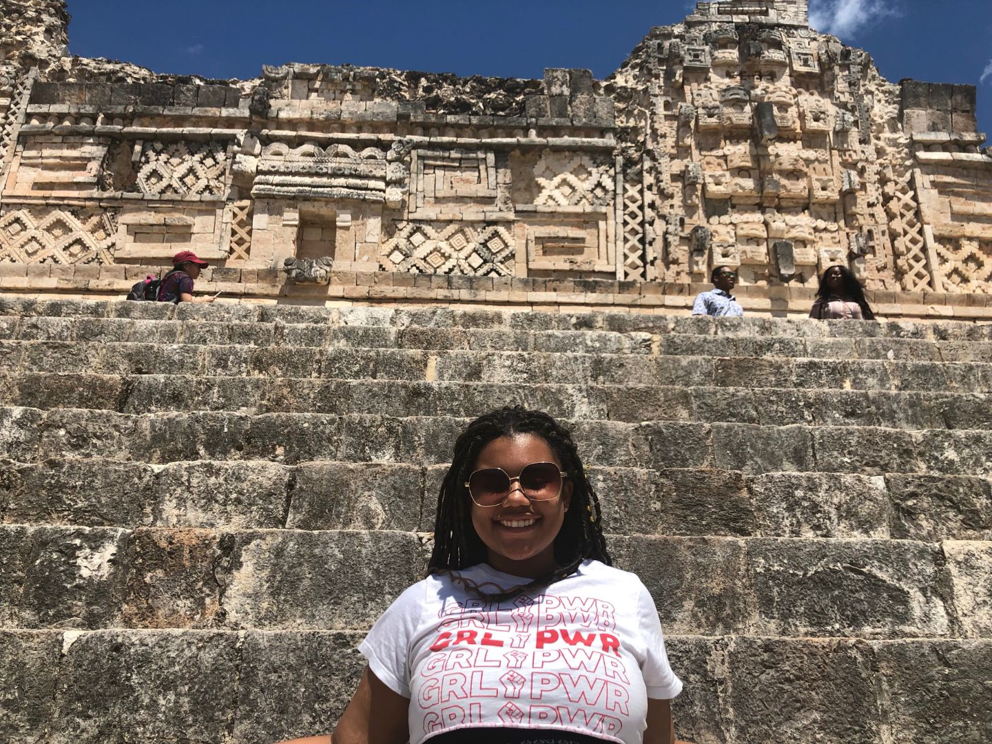 """Williams smiles in front of stone ruins, wearing a shirt that says """"GRL PWR""""."""