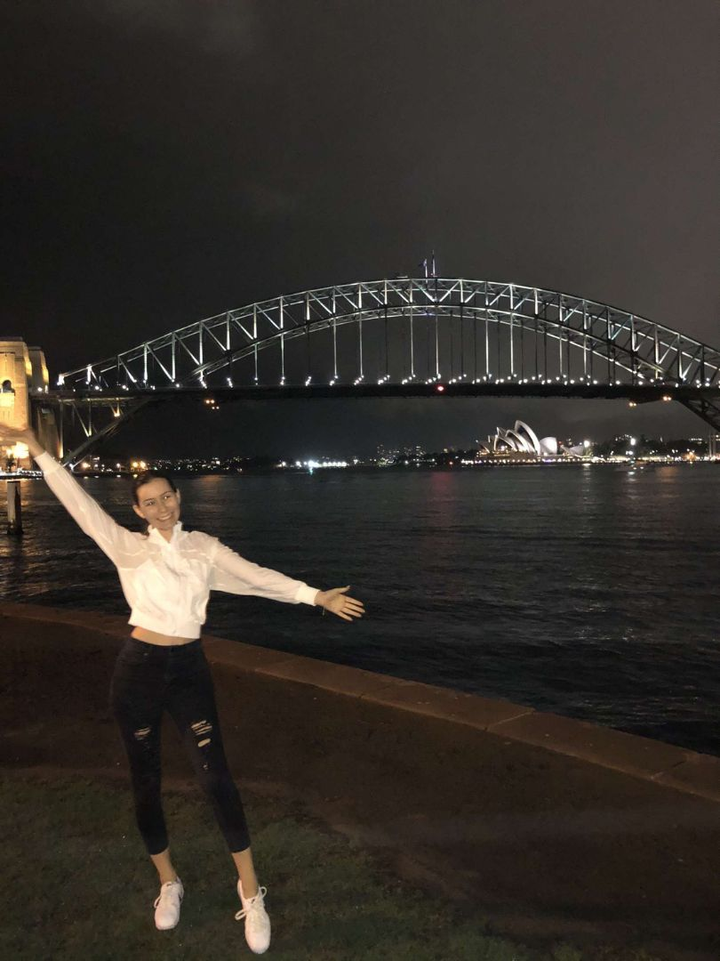 Katarina with arms up at night by Sydney Harbor Bridge in Australia