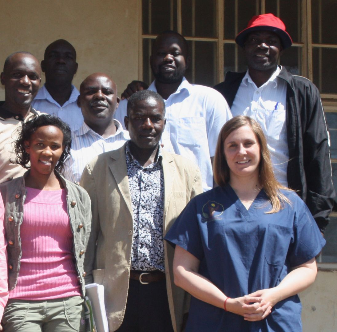 Sarah stands smiling with seven of her Ugandan colleagues on a bright sunny day.