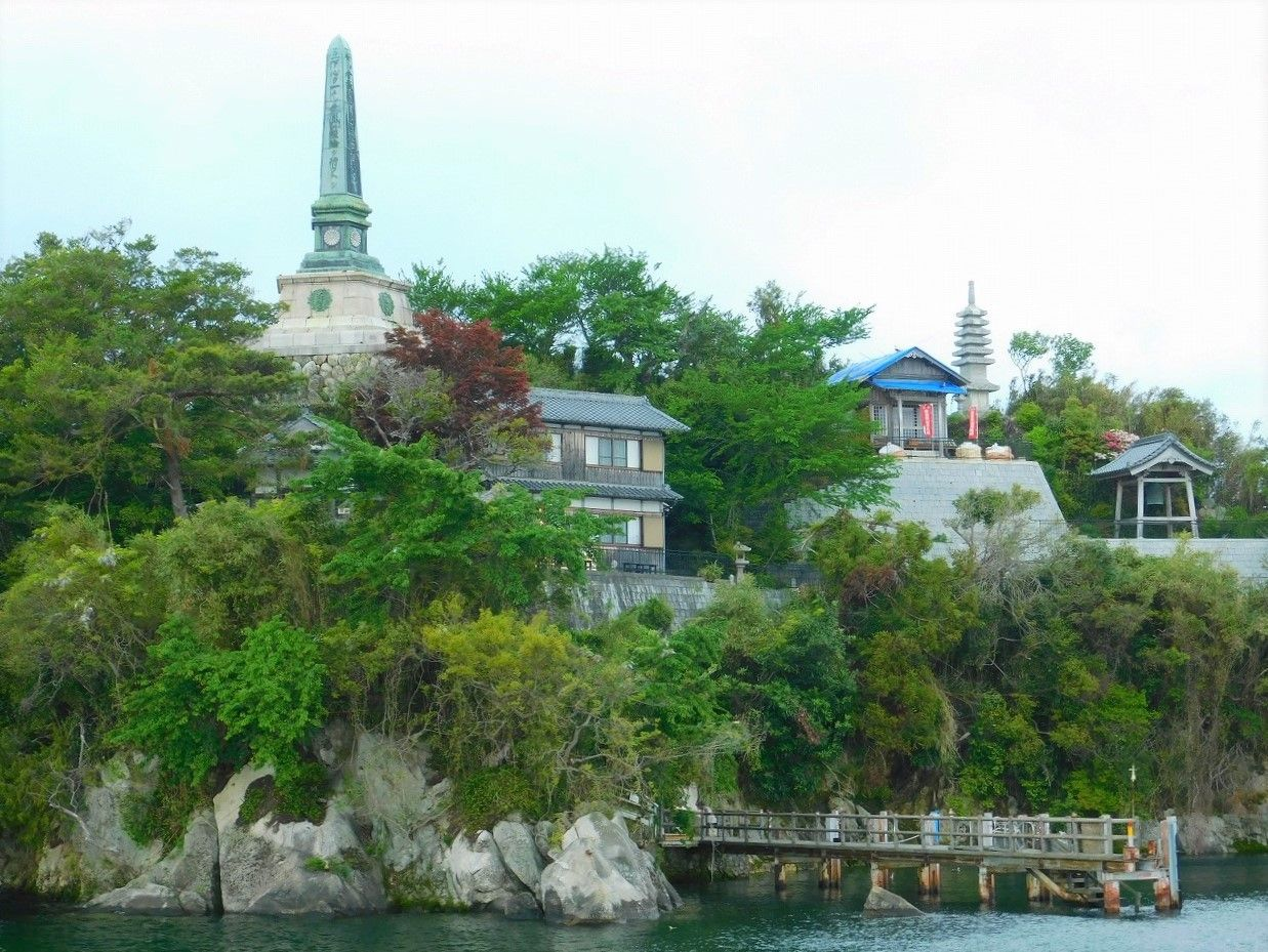 a small rocky island with trees and a temple