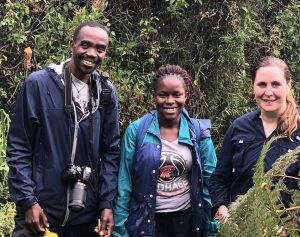 Sarah Corner stands with two Ugandan veterinarians in front of a lush green background.