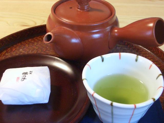 a cup of green tea next to a teapot