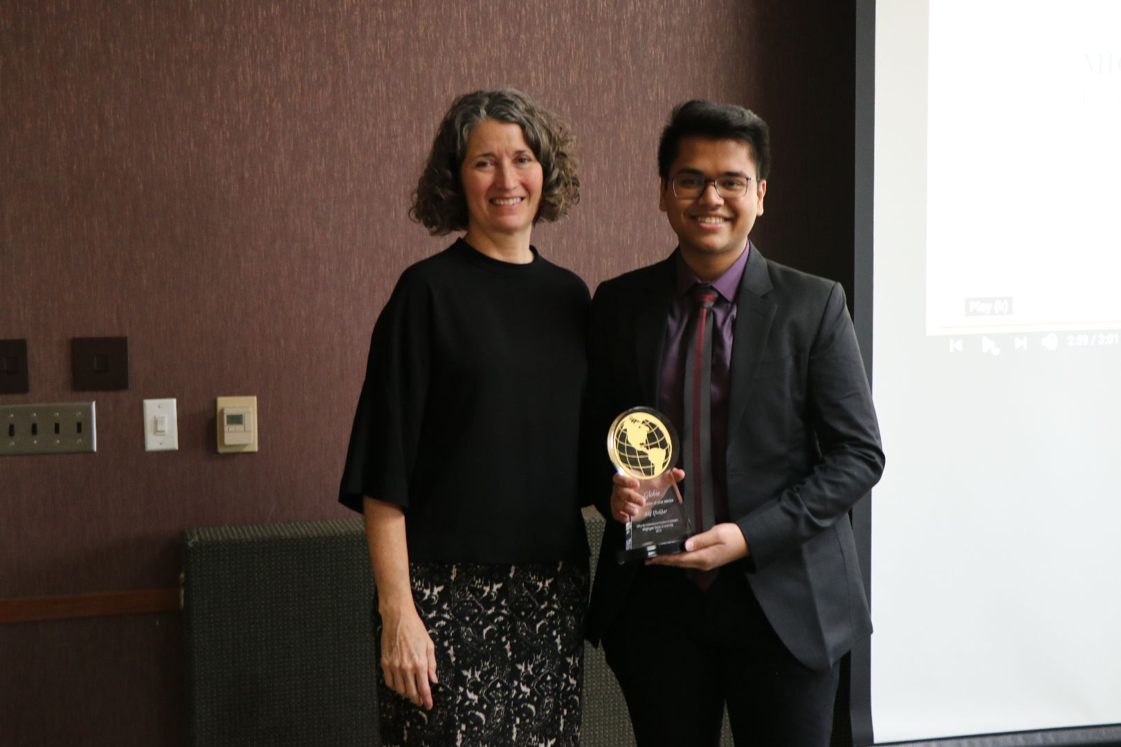 Woman standing with young man, who is holding a Globie Award trophy.