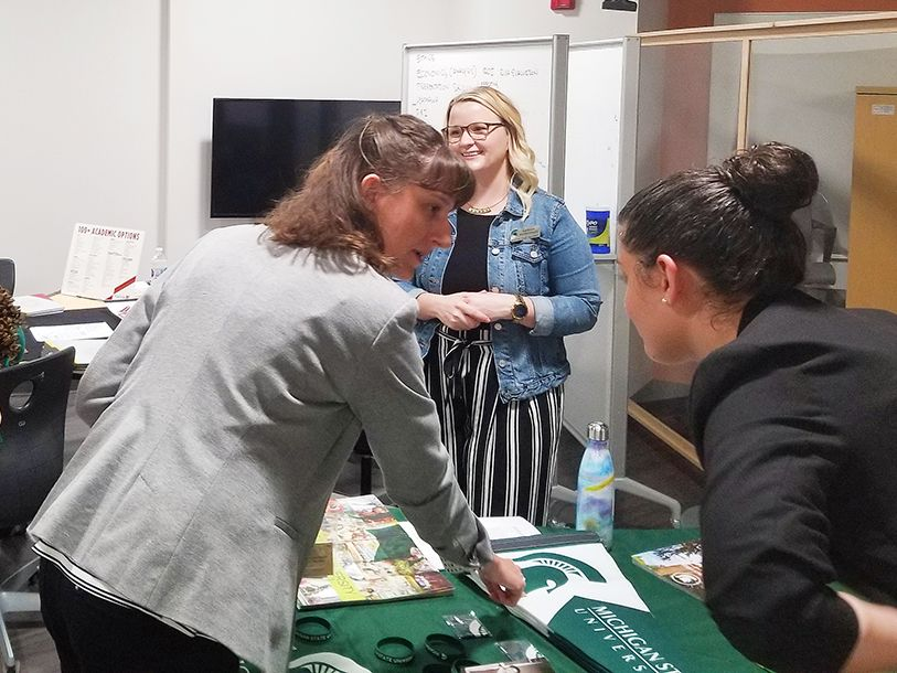 EducationUSA advisers talking to admissions counselors from MSU learning about what MSU has to offer international students. Three women standing around a table with MSU material.