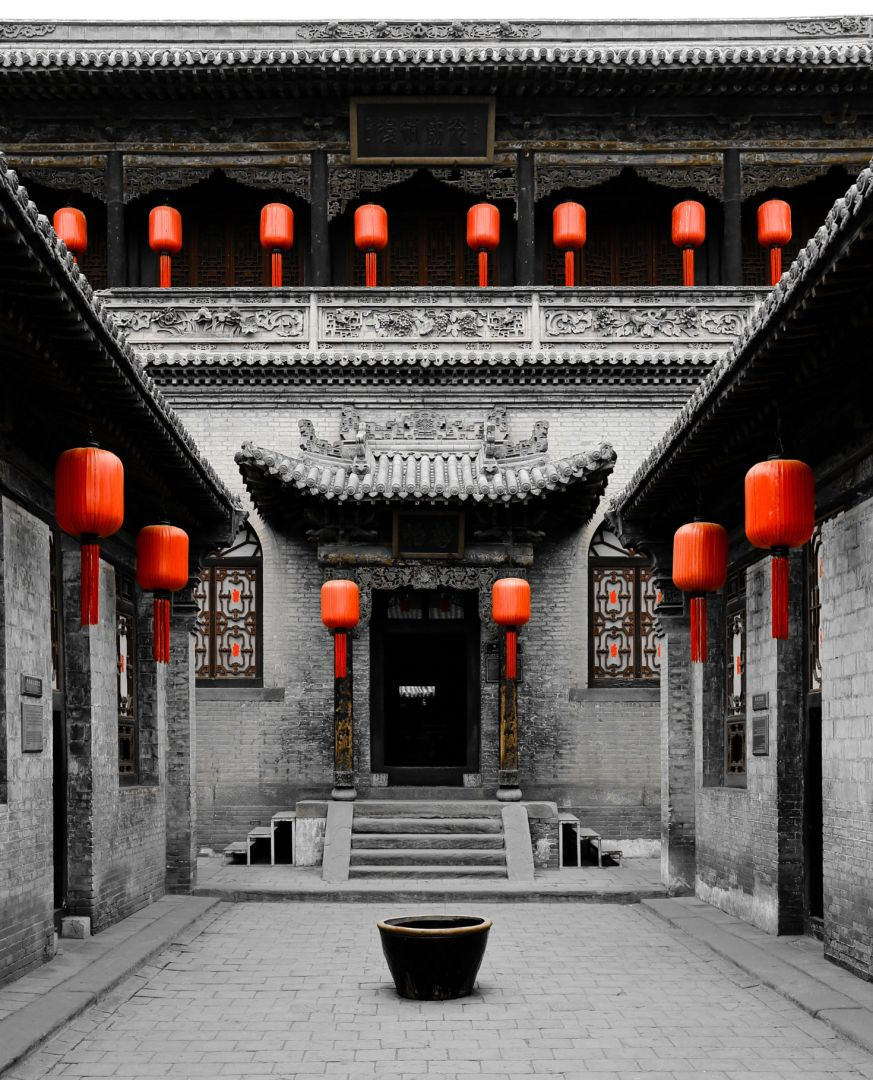 The empty courtyard of an old, gray, two-story Chinese building with intricate carvings on its facade. Bright orange lanterns hang on the stone awnings. A single, large, empty bowl sits in the middle of the courtyard, leading to a set of stairs and doorway into the building.