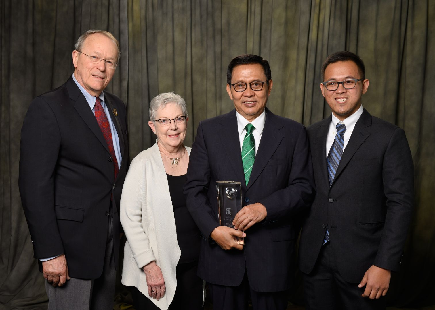 Award recipient Suyanto [male] is pictured center in green tie holding award with three guests