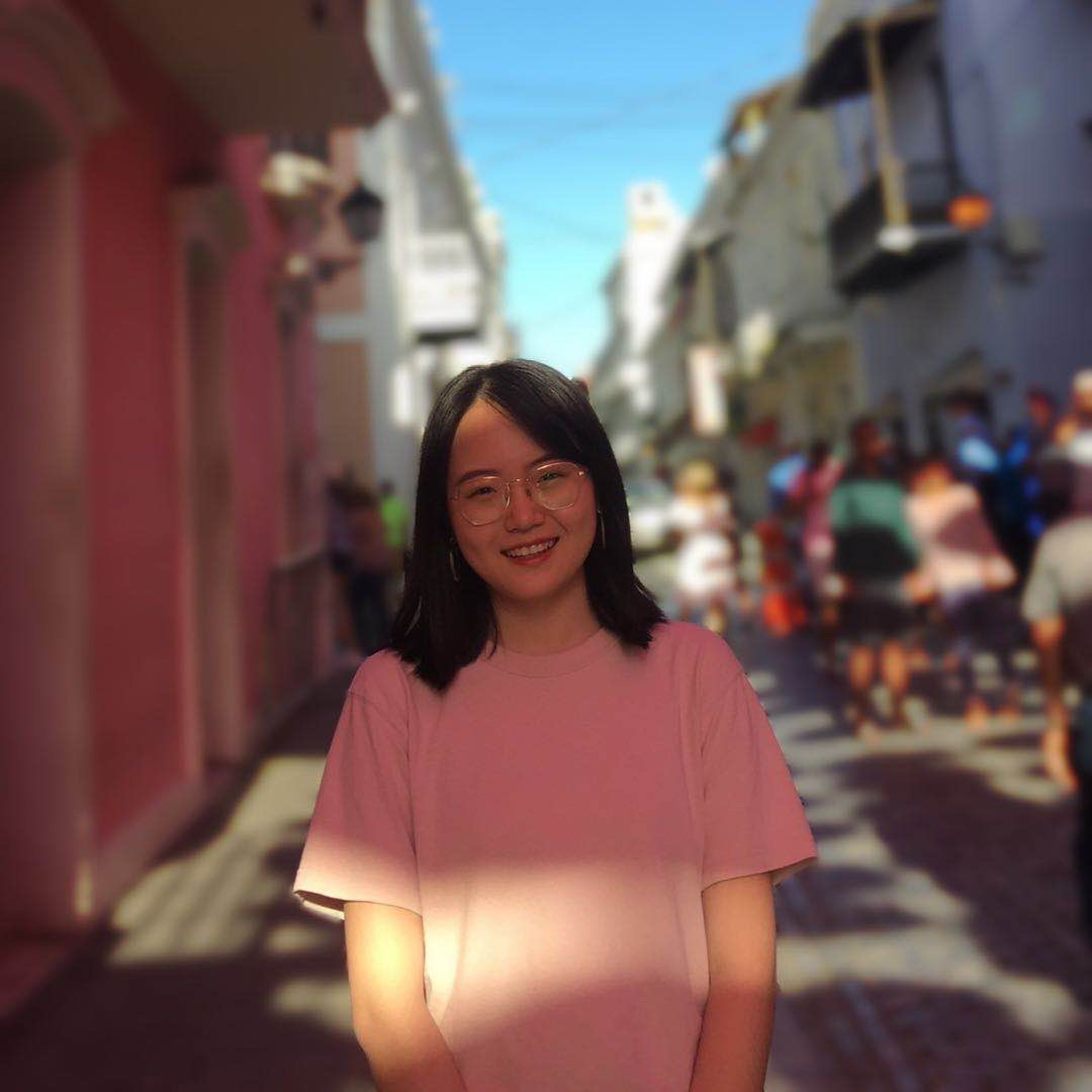 Melody stands smiling and in focus with a blurry city street scene behind her.